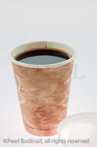 Disposable coffee cup full of black coffee on a white 