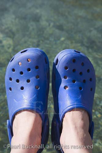 Pair of person's feet wearing blue Crocs against blue- green clear sea water   Keywords: beachware seaside modern new trendy  fashion craze plastic shoes footwear