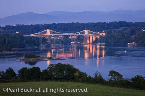 View of the Menai Strait with the Menai suspension  bridge illuminated at night. Menai Bridge  (Porthaethwy), Isle of Anglesey (Ynys Mon), North  Wales, UK, Europe