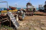 Fishing boats and sign for fresh herrings on the south 