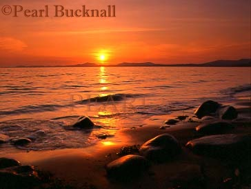 SUNSET ACROSS TREMADOC BAY from the beach.  Llanfair, Gwynedd, Wales, UK  Keywords: beach coast red reflection scenic sea sunset  water
